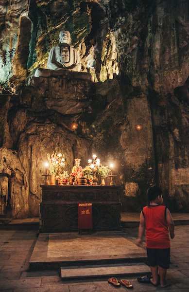 Giant Buddha statue in dimly lit cave sits above a buddhist altar. Marble Mountain, Da Nang