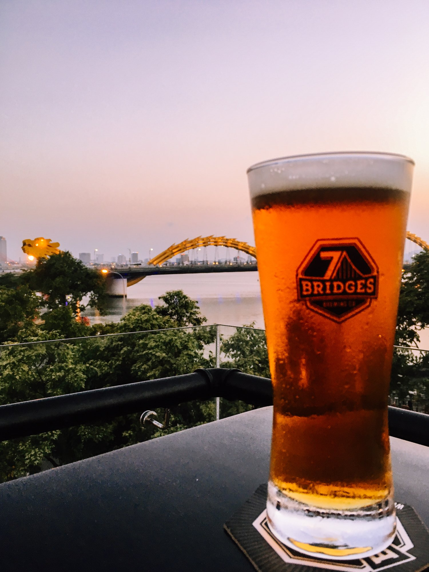 drinking a red ale at 7 Bridges Brewery in Da Nang Vietnam with a view of the Dragon Bridge