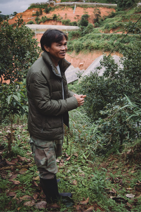 The proud Dalat coffee farmer stands in front of his coffee plants