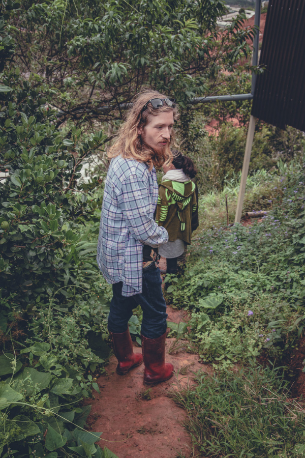Adam, in his red boots, admires the lush green plants all around