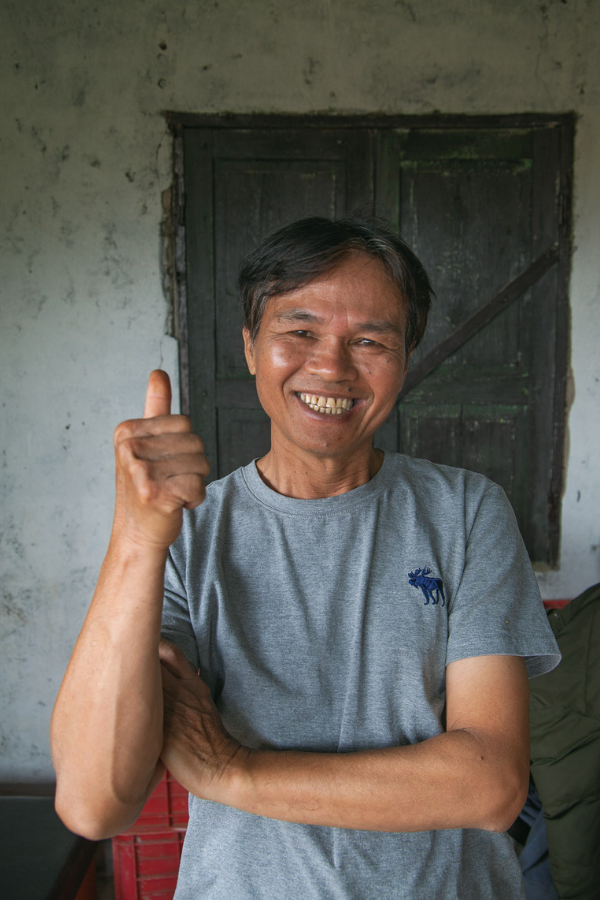 Son, the coffee farmer, smiles and gives a thumbs up