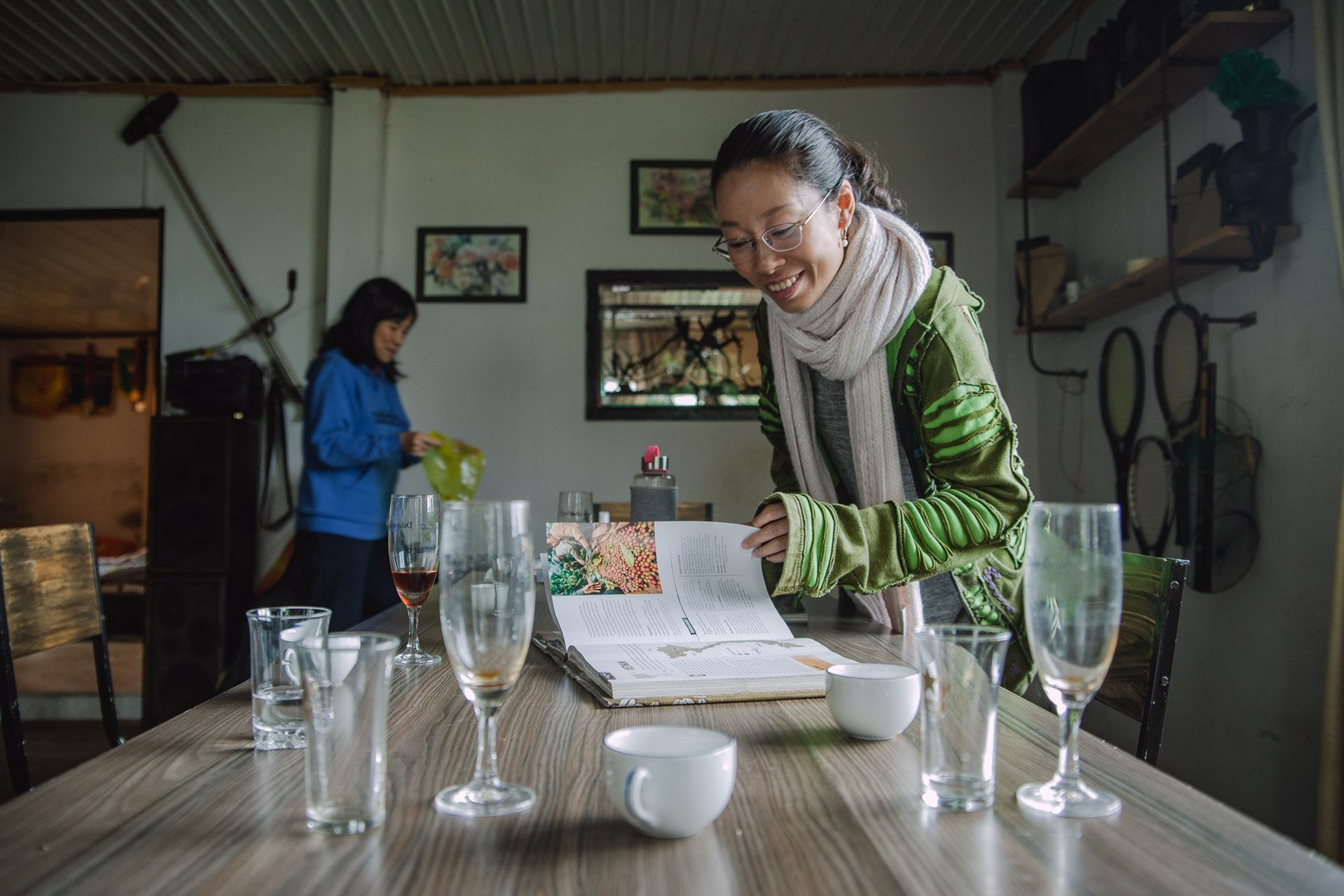 "Linh browses the ""Atlas of Coffee"" inside the coffee workshop"