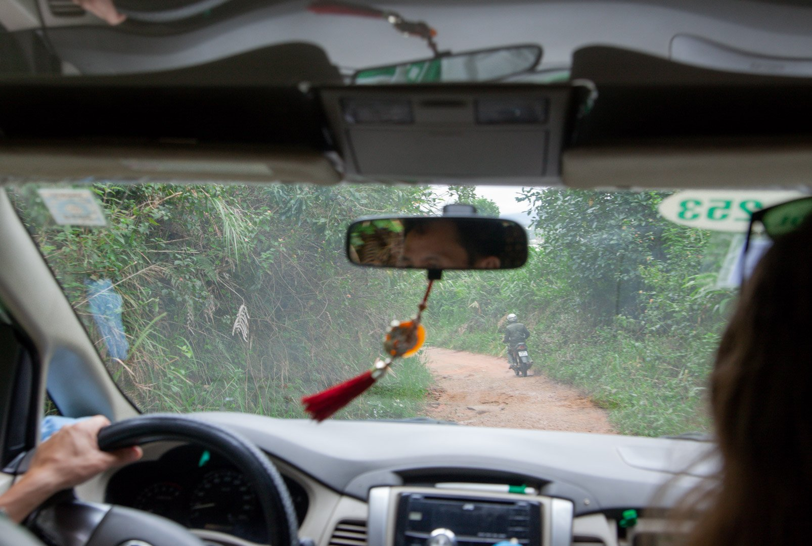 From the back seat of the taxi, we can see the coffee farmer on his motorbike ahead on the dirt road