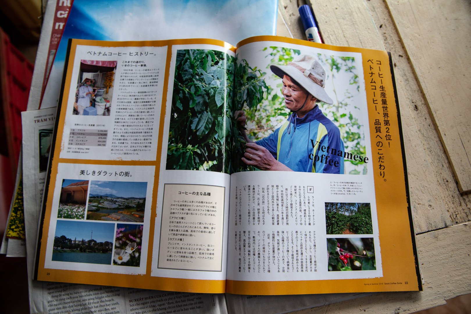 An open magazine displays photos of the dalat coffee farm