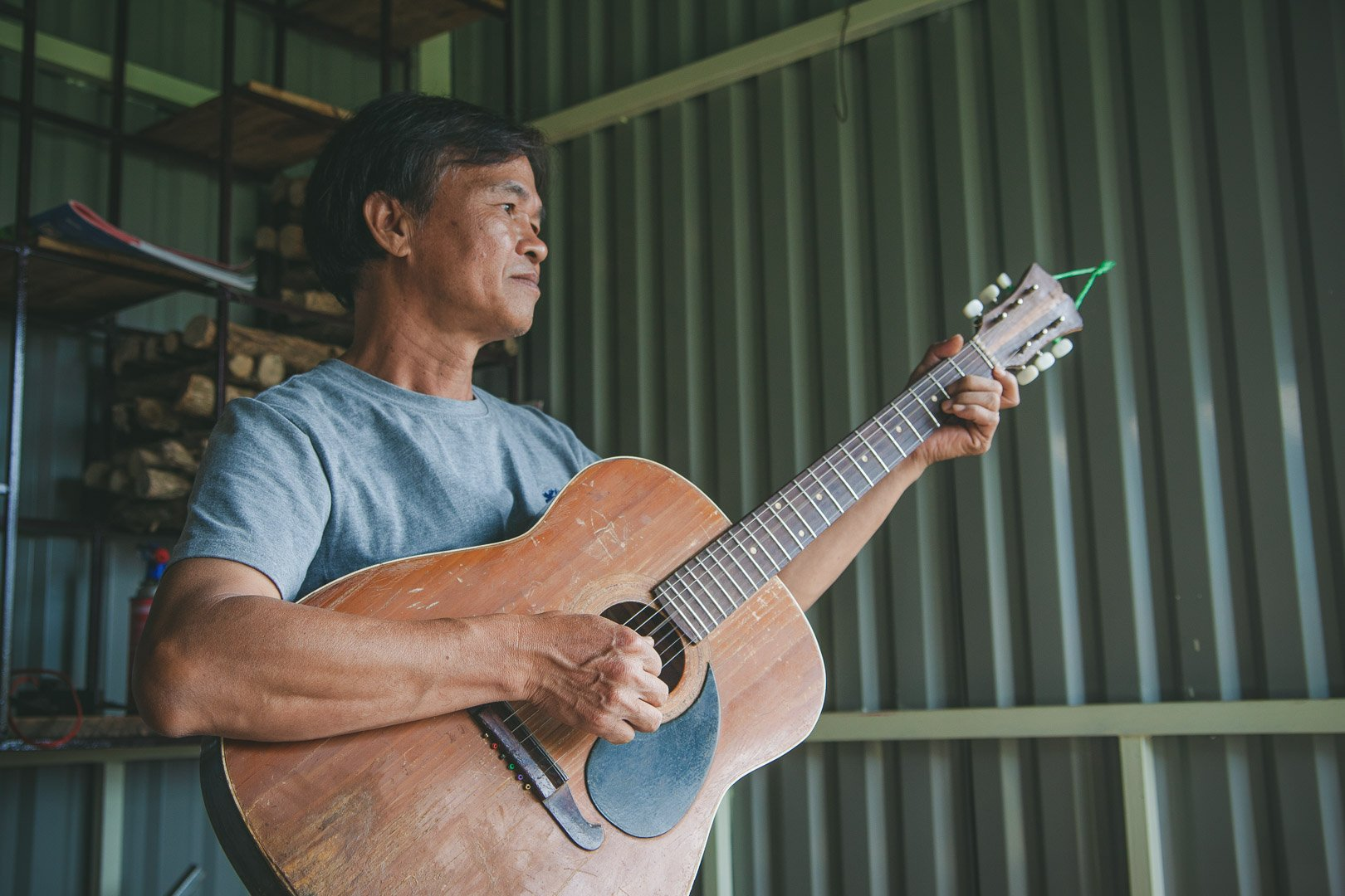 The coffee farmer, holding a guitar, sings us a song to end our tour