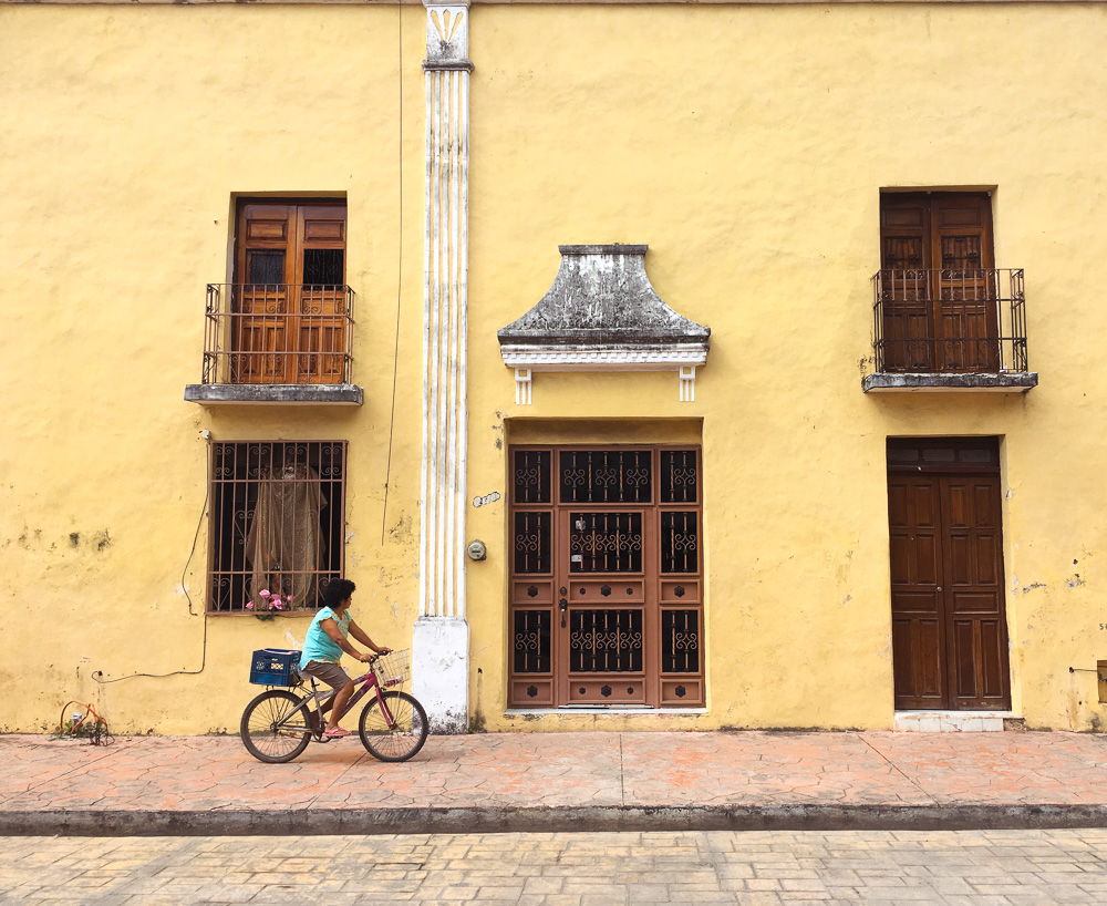 woman in blue riding past a yellow colonial building on a red bicycle.