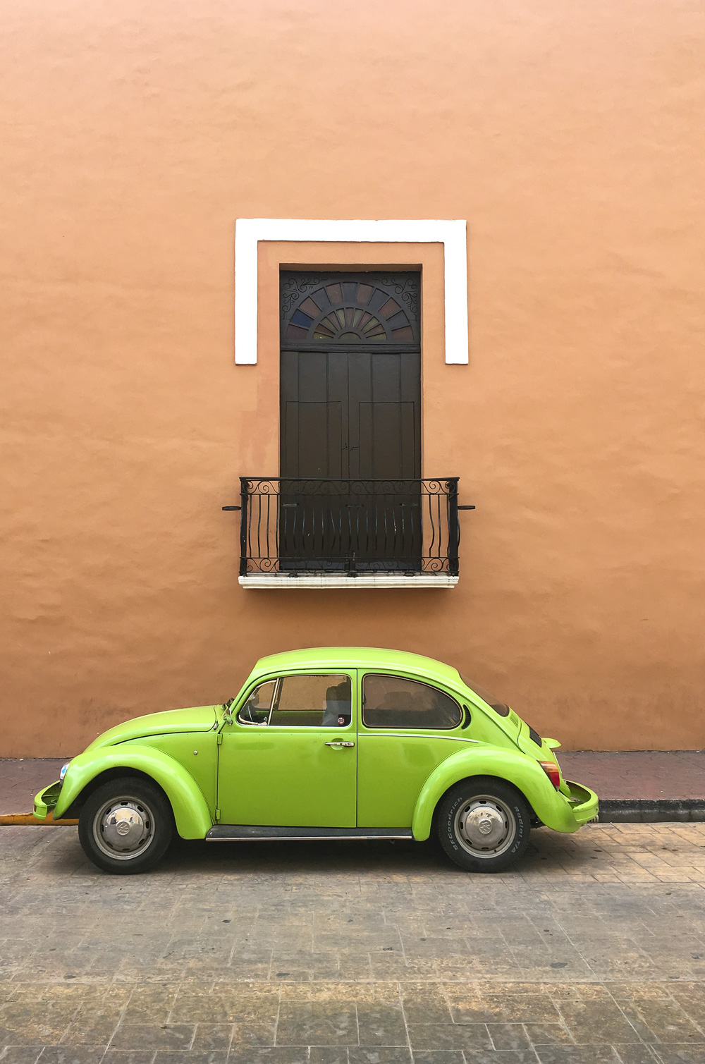 Green Volkswagen Beetle in front of orange colonial building