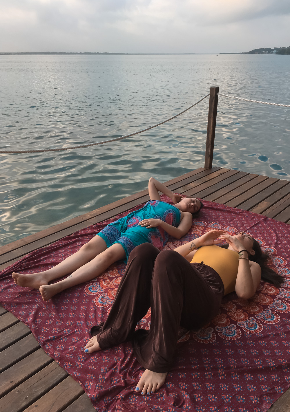 two girls laying down on the dock by the blue lake
