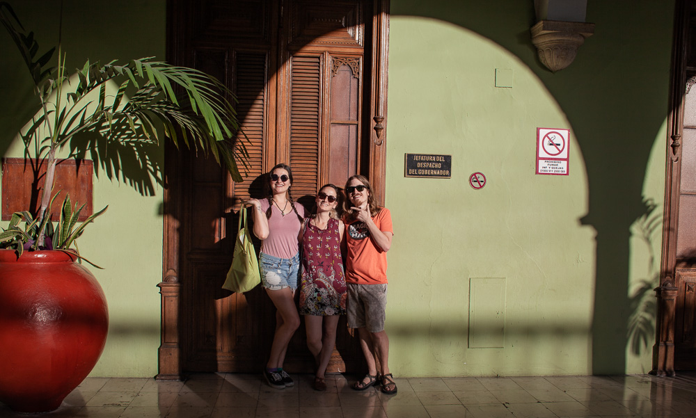 group pose in front of green wall in Palacio publico in Merida, Mexico