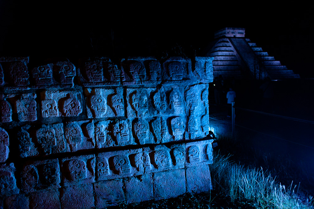 Chichen Itza carved skulls in stone wall, lit by blue light at night.