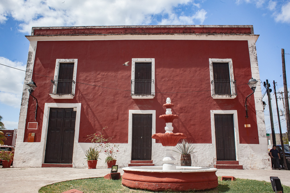 Red Colonial Building with red and white fountain. Valladolid, Mexico