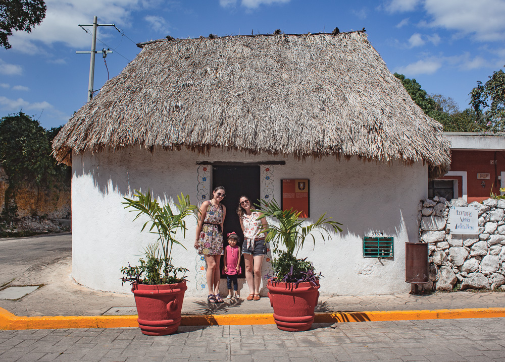posing with a little girl at a Mayan Palapa House in Valladolid