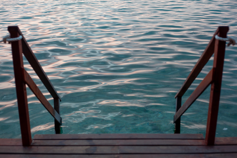 Staring down the stairs into turquoise water. Bacalar, Mexico