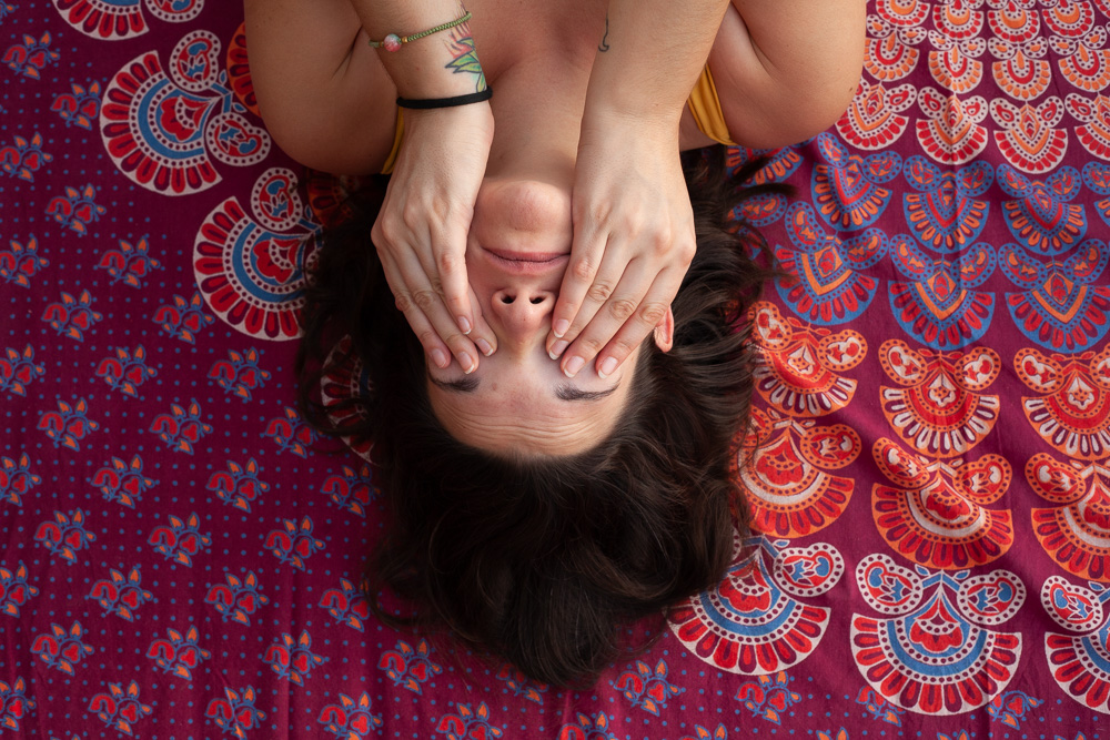 Girl laying down on mandala tapestry, covering her face with fingers