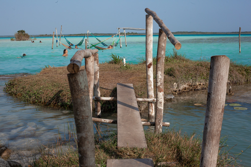 narrow wooden bridge extends out to a tiny island surrounded by turquoise water.