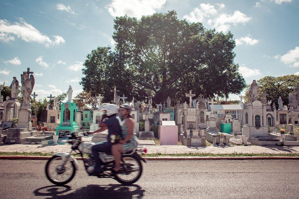 Couple rides motorbike through cemetery