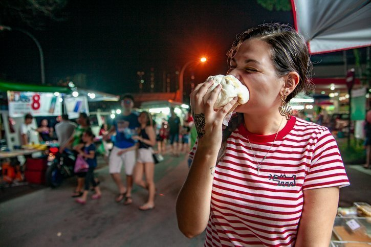 Gabi eating a giant steamed bun bao at the Tanjung Bungah night market