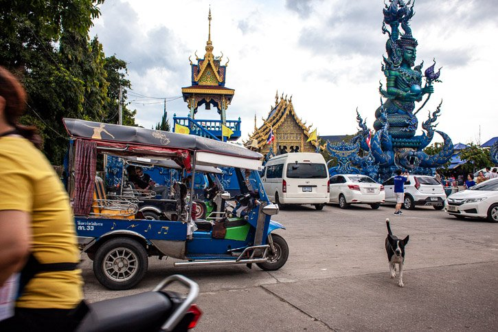 Tuk Tuks and tour vans wait for tourists outside the Blue Temple in Chaing Rai